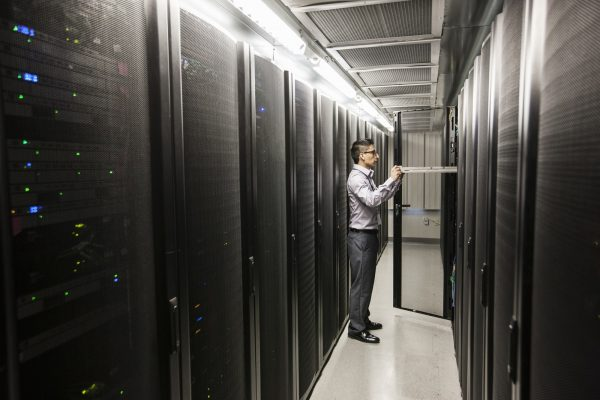 Hispanic man technician doing diagnostic tests on computer servers in a large server farm.